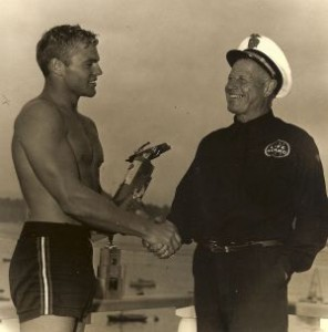 George 'Cap' Watkins presents Tommy Zahn with a paddle-boarding trophy.