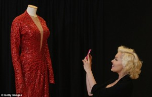 Suzie Kennedy poses with Marilyn's red dress from 'Gentlemen Prefer Blondes'