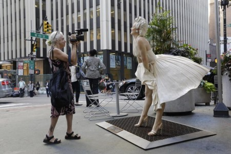 Documentary filmmaker Kathy Brew does a video of a Marilyn Monroe sculpture, while making a film about artist Seward Johnson, whose 18 sculptures have been placed in the pedestrian islands on Broadway in the city's garment district.